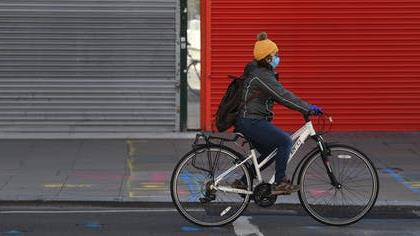 Exit strategy: A young cyclist passes a closed shop on London's Oxford Street PICTURE: EPA-EFE/NEIL HALL
