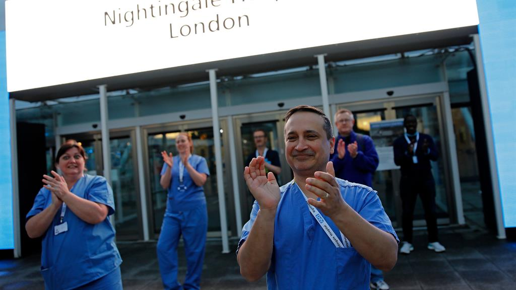 Reason to be cheerful: NHS staff join in the clapping for carers outside the Nightingale Hospital in London's Docklands, which is to be put on hold PICTURE: AFP/GETTY