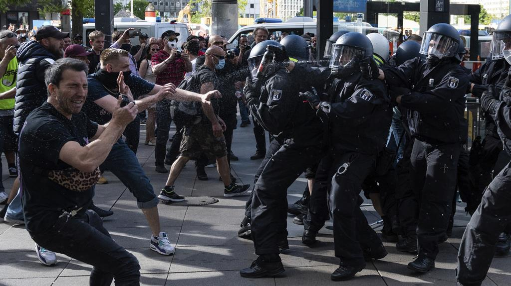 Taking the sting: A demonstrator winces as police use pepper spray during rally at Berlin's  Alexanderplatz on Saturday PICTURE: AP