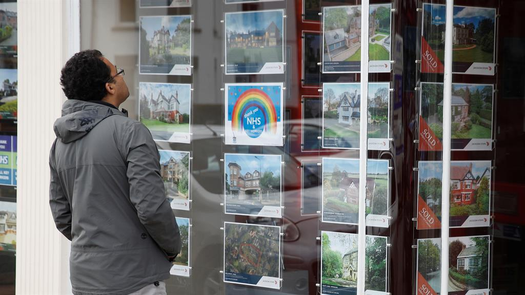 Window shopping: A man studies an estate agent's display yesterday PICTURE: REUTERS