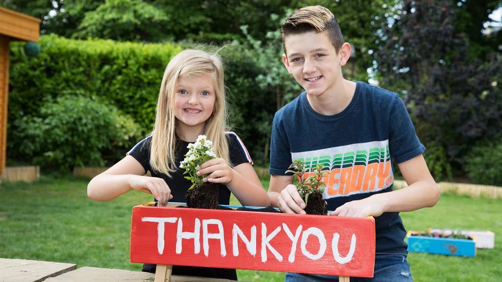 Saying it with flowers: Hollie and Brooklyn Peart painted planters as gifts for key workers PICTURE: NATIONAL LOTTERY/PA