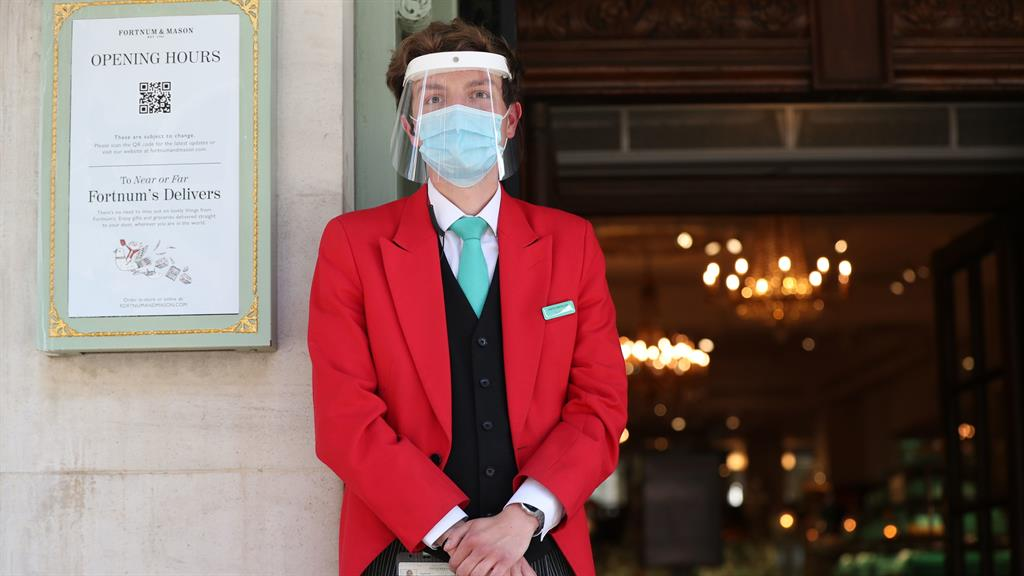 Red alert: A doorman wears a mask and visor at Fortnum & Mason in London PICTURE: PA
