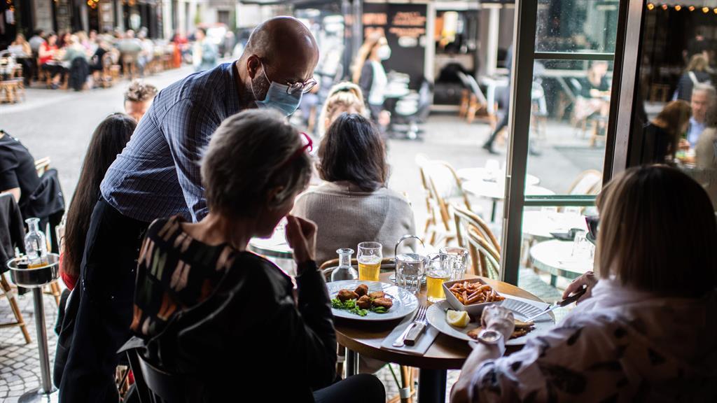 Bon appétit: Friends enjoy lunch inside a Parisian restaurant yesterday PIC: AFP