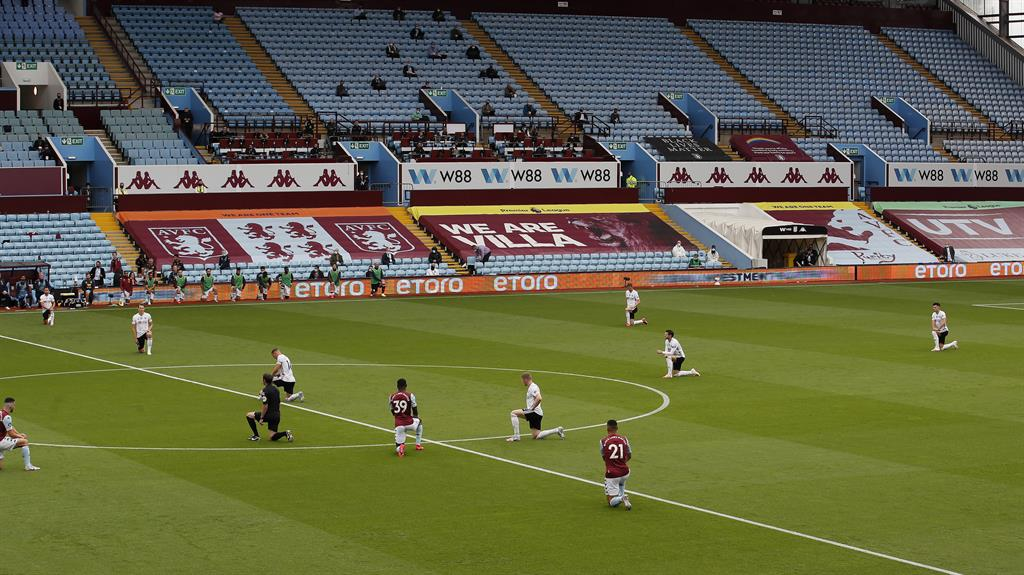 Emotional: Players 'take a knee' at Villa Park as the Premier League kicks off in an empty stadium PICS: REUTERS/GETTY/SPORTIMAGE