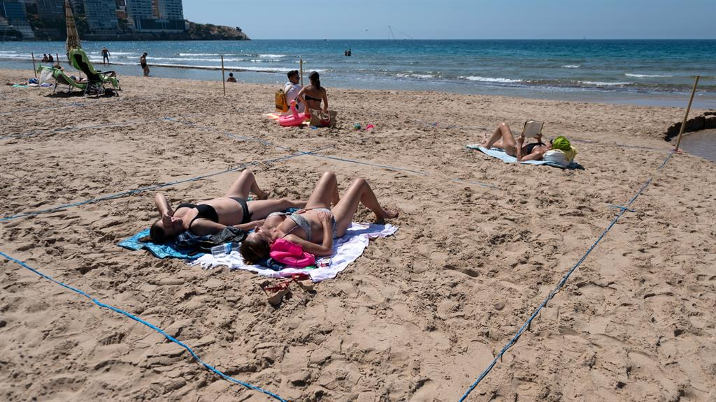 Strung out: Beachgoers sunbathe in roped-off squares of Benidorm's Poniente beach to enforce social distancing PICTURE: AFP