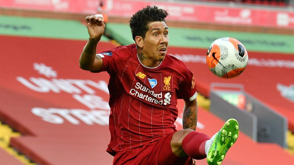 Balancing act: Roberto Firmino in front of the sponsors' logos at Anfield PICTURE: GETTY
