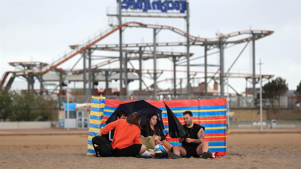 Toughing it out: People shelter under umbrellas in Skegness yesterday PICTURE: PA