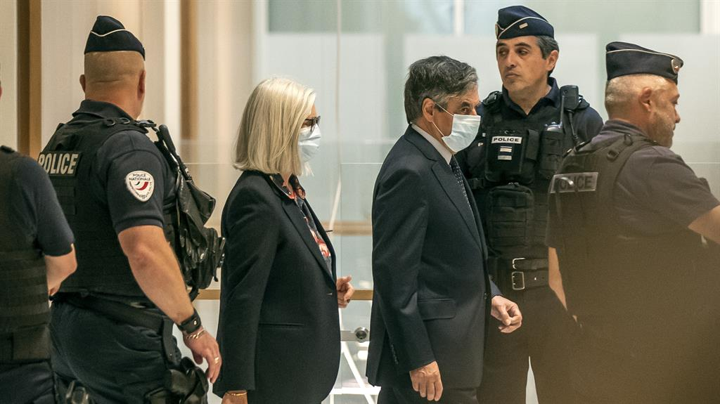 Masked villains: François Fillon and his wife Penelope arriving at court in Paris yesterday PICTURE: AP