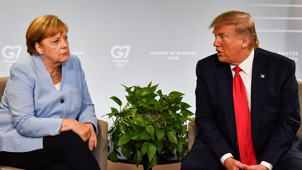 Calm front Angela Merkel listens to Mr Trump at last year's G7 Summit