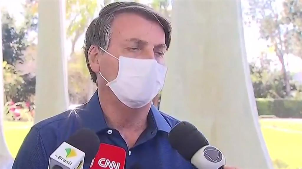 Still defiant: Jair Bolsonaro reveals his test result, before pulling off his mask (below)