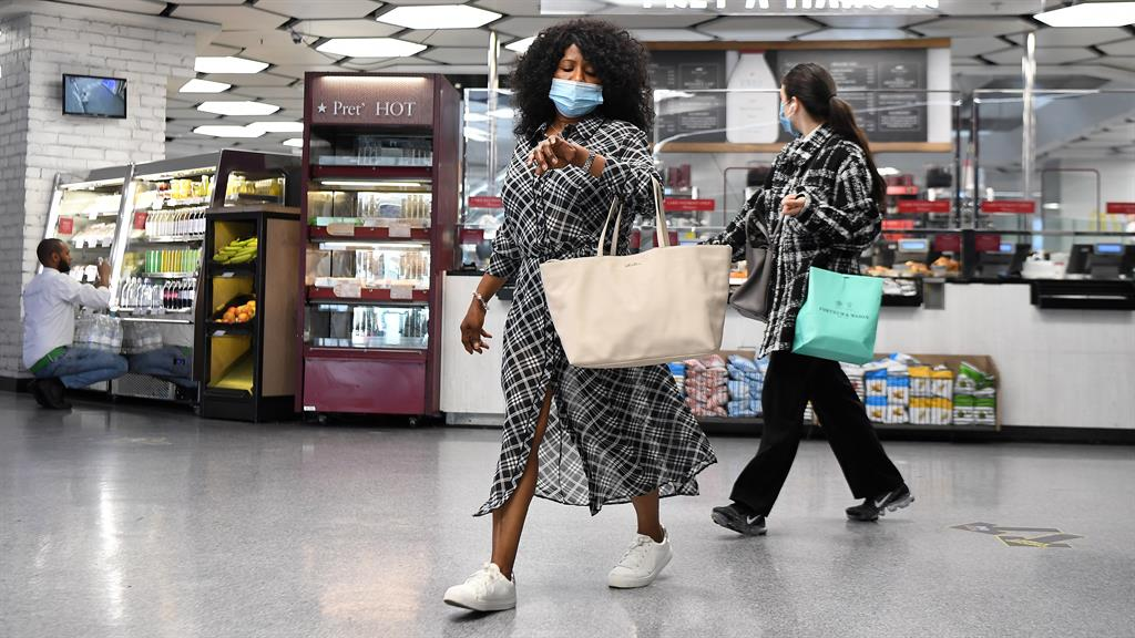 Ahead of the curve: Shoppers at a complex in London already wearing masks PICTURE: EPA