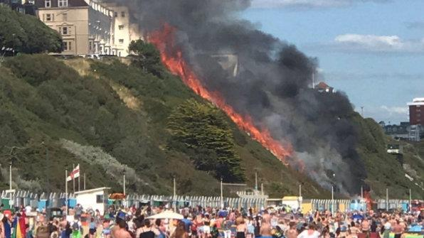 Heat rising: Hundreds watch as the fire shoots up the cliff face PICTURES: UK NEWS IN PICTURES