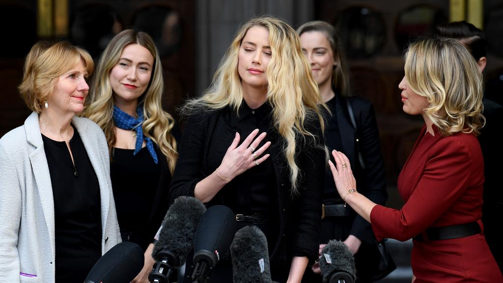 Team Heard: Amber with her supporters. yesterday, making her statement on the. court steps PICTURE: GETTY