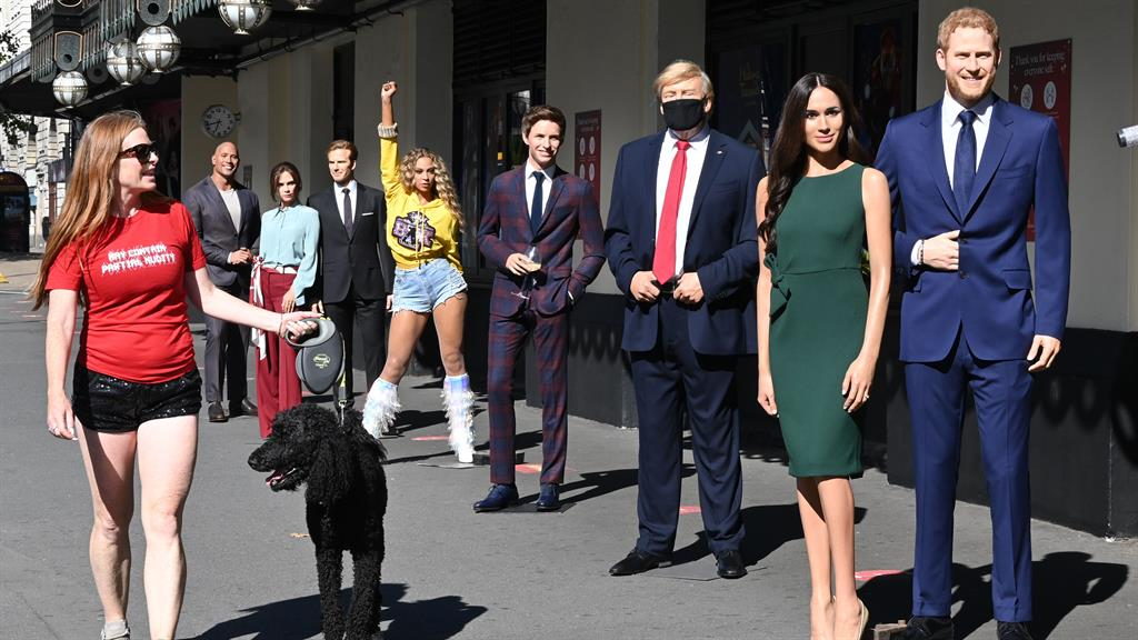 Don't Trump the queue: A dog walker admires waxworks led by Trump, Harry and Meghan PICTURE: REX