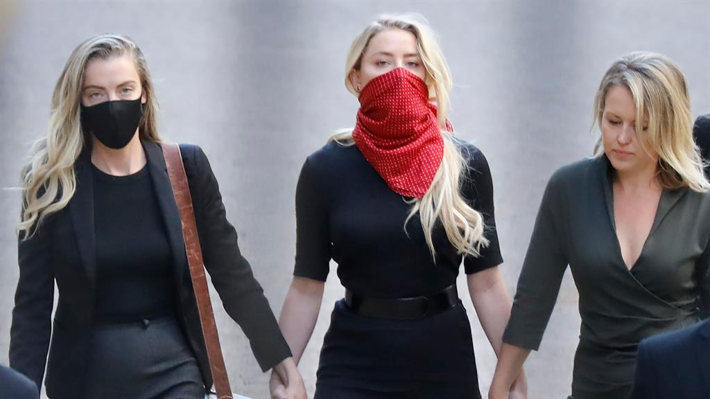 Holding hands Amber Heard with her sister Whitney and lawyer Jennifer Robinson yesterday