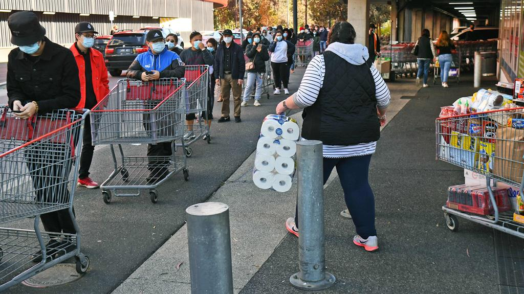 Stocking up: Shoppers wait in line outside supermarket yesterday PICTURE: GETTY