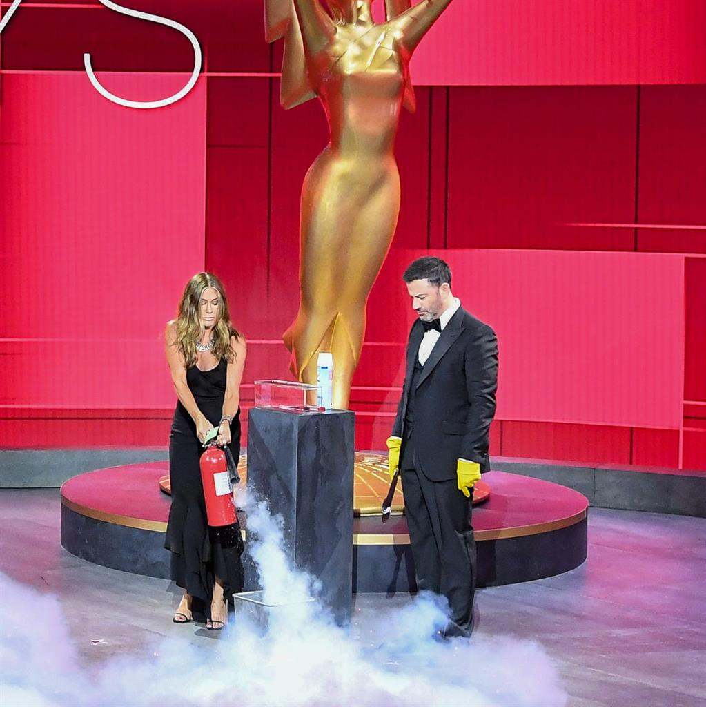 Proceed with caution: Jennifer Aniston and Jimmy Kimmel sanitize the winner's envelope while presenting the Emmy for outstanding lead actress in a comedy series PICTURES: EPA