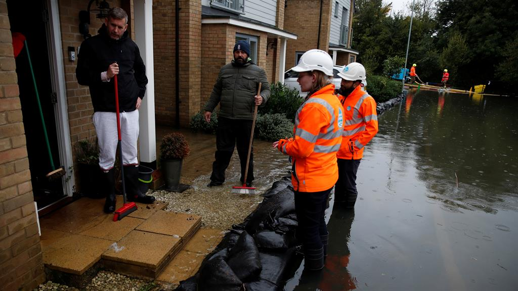 Waterlogged: Flooded residents in Hemel Hempstead talk to utility workers PICTURE: REUTERS