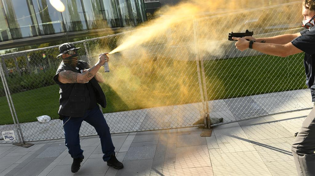 Shocking: Guard points pistol as protester sprays Mace. Below: He falls to his knees, dropping gun on pavement, as armed cops swoop PICTURE: DENVER POST/AP