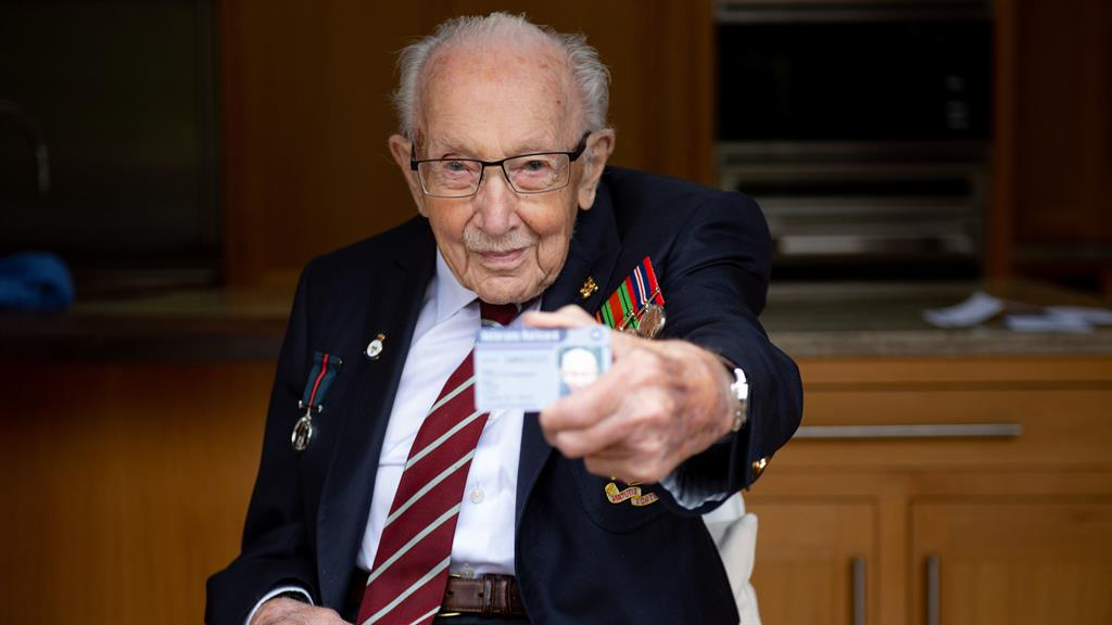 First proud owner: Sir Tom, 100, displays discount card, below PICTURE: PA