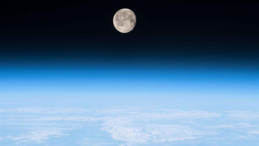 Photo of a nearly full Moon shining brightly on the Earth's atmosphere, taken from the International Space Station PICTURE: NASA