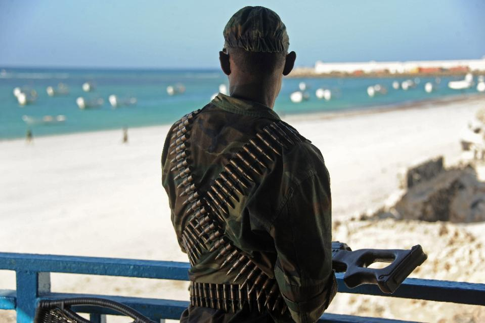 A Somali soldier looks at the Lido beach from the terrace of the Lido seafood restaurant on January 22, 2016 following an overnight attack (AFP Photo/Mohamed Abdiwahab)