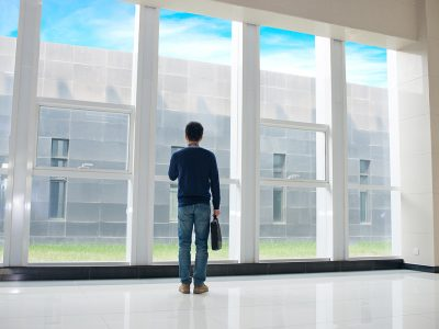 A single man with a briefcase stands at a window, looking out over a building