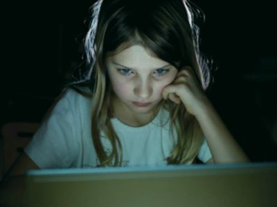 Young Girl looking at a computer head resting on her fist, looking sad