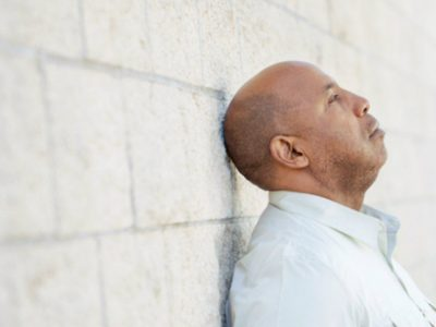 middle aged mixed race man leaning against a white stone wall.