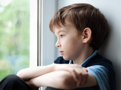 young Boy looking sad looking out the window, arms crossed resting on his knees