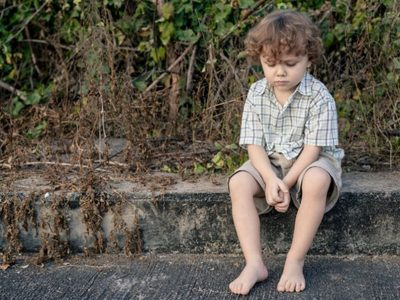 Young boy sitting on a step, barefoot looking sad
