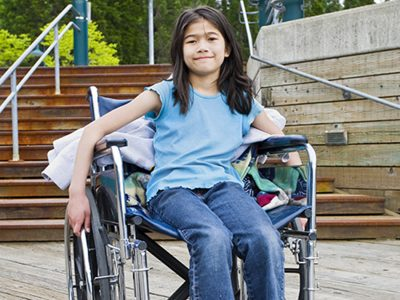 Disabled girl in a large wheelchair, holding onto the wheels