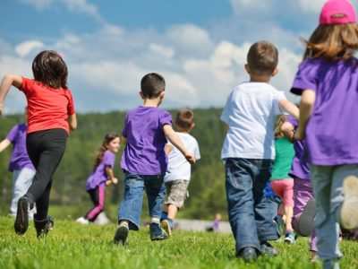 group of children running in a field,