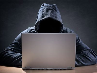 Man with face blacked out in hoodie looking at a laptop,