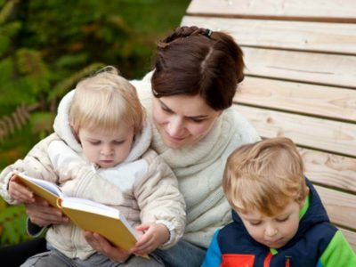 Woman sat with two children outside, reading a book.