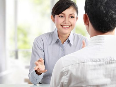 Woman and man in a meeting, woman facing the camera, man has his back to the camera, woman is talking to man and smiling