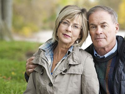 Older Couple looking at the camera, man has his arm around the woman and hand on her shoulder. they are in a park