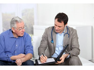 Male Doctor with an elderly male patient writing notes on a folder. stethoscope around his neck