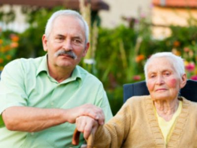 Elderly Couple sitting next to each other holding hands on top of her walking stick