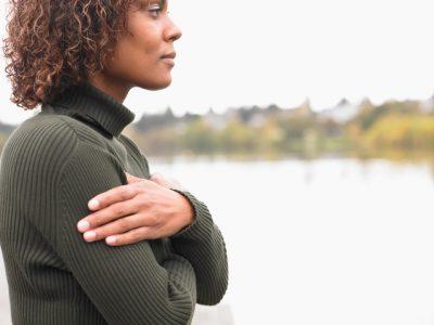 Woman wearing a dark green jumper hugging herself by a lake