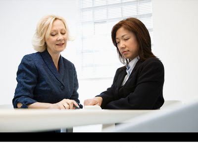 two women having a meeting, both are looking at a document on the table