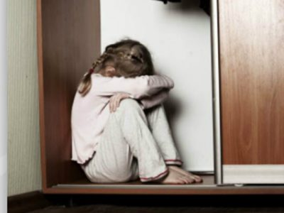 Little Girl in a wardrobe bent over crying and hiding her face