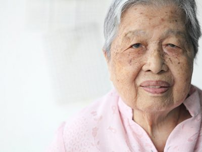 old Woman in pink blouse smiling and looking at the camera