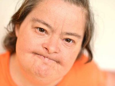 Woman with Learning disabilities in an orange top pursing lips and look at the camera