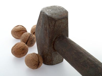 Metal Mallet next to some Walnuts