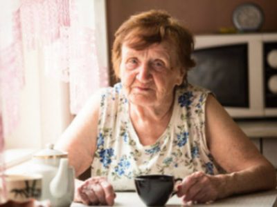 elderly lady sat at the table in a kitchen holding a black mug looking at the camera