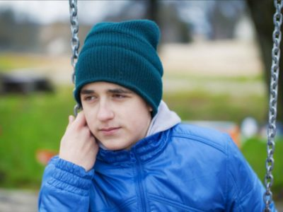 teenage man on a swing wearing a green beanie hat and a blue shell jacket.