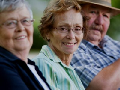 three older people sat smiling at the camera.