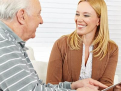 Young Blonde woman showing an old man how to use a tablet