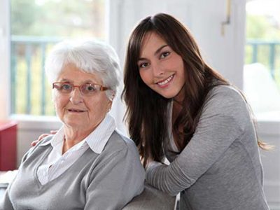 Woman sat behind a chair with an elderly lady both are smiling at the camera